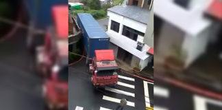 Водитель виртуозно проводит грузовик через узкий просвет между домами.